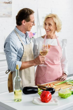 smiling senior couple clinking with glasses of wine during cooking at kitchen and looking at each other
