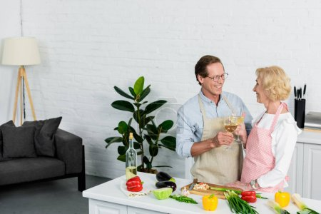 happy senior couple clinking with glasses of white wine during cooking at kitchen