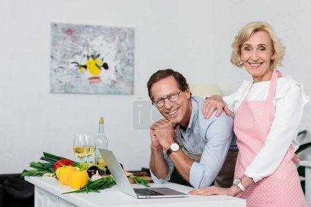 smiling senior couple looking at camera at kitchen