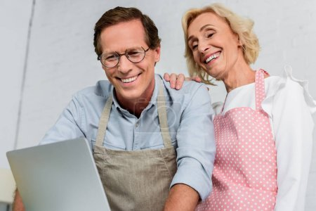 low angle view of smiling senior couple in aprons looking at laptop at kitchen