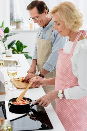 side view of senior couple cooking vegetables on frying pan and cutting vegetables on wooden board at kitchen