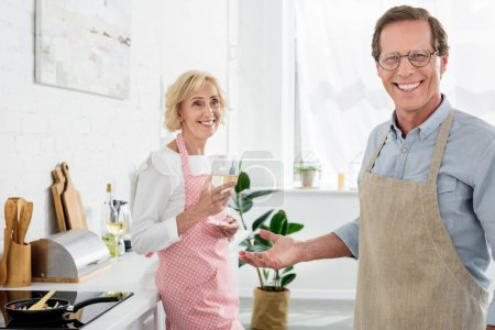 Photo for Happy old man in apron and eyeglasses smiling at camera while wife drinking wine in kitchen - Royalty Free Image
