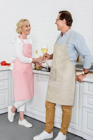 happy senior couple drinking wine and smiling each other while cooking together in kitchen