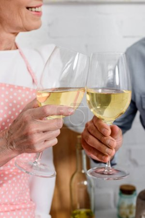 cropped shot of elederly couple clinking glasses of wine
