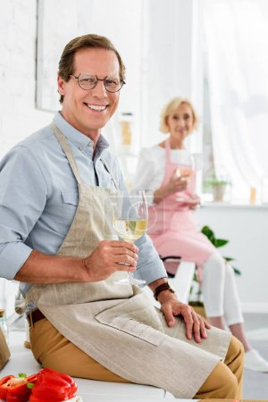 Photo for Happy senior couple holding glasses of wine and smiling at camera while cooking together - Royalty Free Image