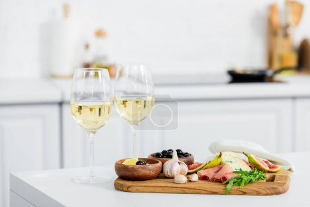 delicious snacks on wooden board and glasses of wine on table