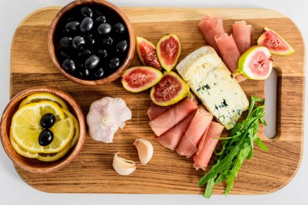 top view of delicious snacks on wooden board on table