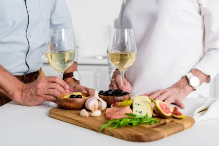 close-up partial view of elderly couple holding glasses of wine while enjoying delicious snacks at home