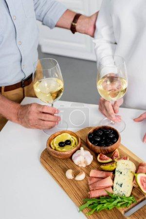 recadrée tir du couple de personnes âgées tenant des verres de vin tout en dégustant de délicieux en-cas à la maison