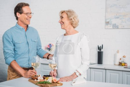 beautiful happy elderly couple talking and smiling each other while drinking wine and eating delicious snacks at home