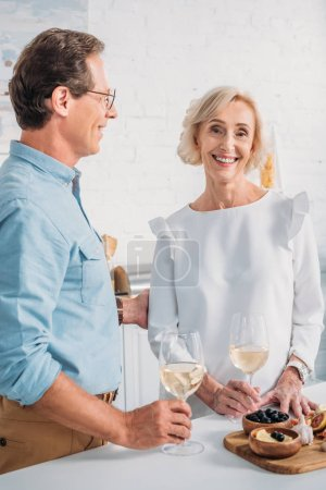 happy elderly couple drinking wine together at home