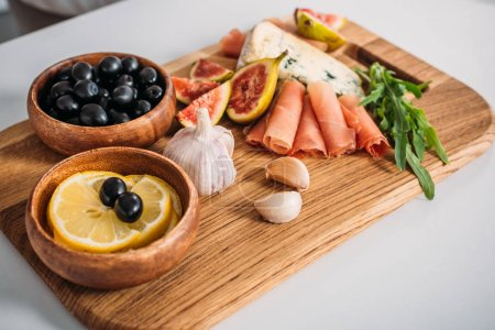 close-up view of delicious snacks on wooden board on table