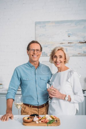 happy senior couple drinking wine and smiling at camera while eating delicious snacks at home