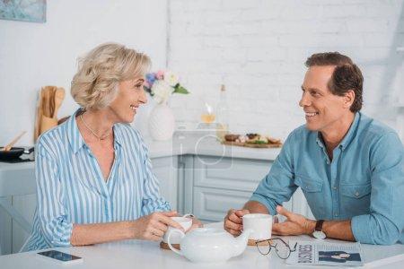 heureux couple senior souriant mutuellement et parler tout en buvant du thé ensemble à la maison