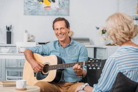 Photo for Happy man playing acoustic guitar and looking at senior wife at home - Royalty Free Image