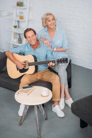 high angle view of happy senior couple enjoying guitar at home