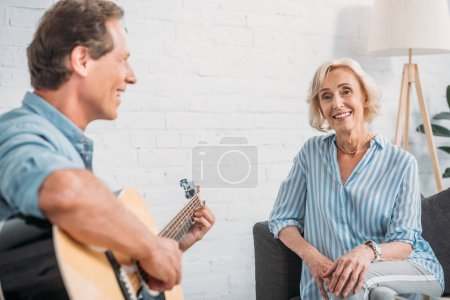 happy man playing guitar to smiling senior wife at home