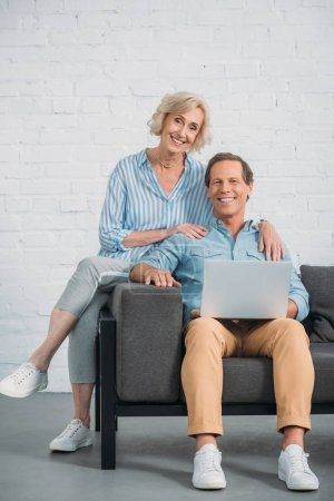 Photo for Happy senior couple using laptop and smiling at camera - Royalty Free Image
