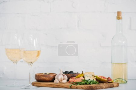 close-up view of glasses and bottle of wine and delicious snacks on table