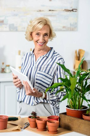 beautiful happy senior woman holding digital tablet and smiling at camera while cultivating plants at home