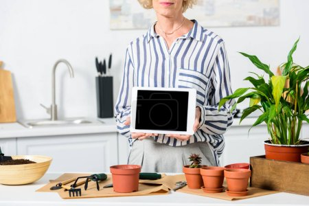 cropped shot of senior woman holding digital tablet with blank screen while cultivating plants at home