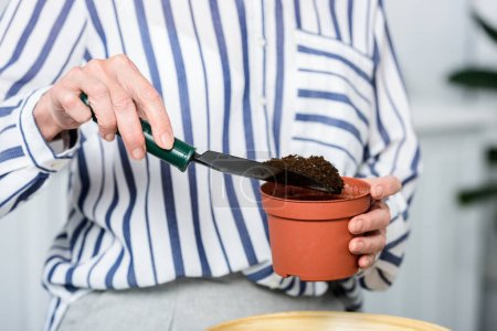 cropped shot of senior woman holding small shovel and pot with soil