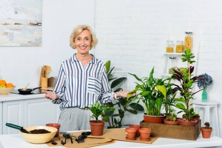 beautiful happy senior woman smiling at camera while cultivating potted plants at home
