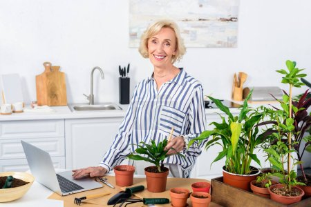 happy senior woman using laptop and cultivating houseplants at home