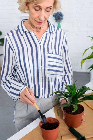 recadrée tir de belle femme senior, cultiver des plantes en pots