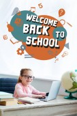 """Adorable kid in eyeglasses smiling at camera while studying with laptop at home with """"welcome back to school"""" lettering and icons"""
