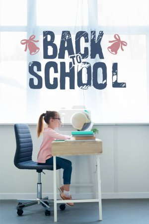 "Side view of little schoolgirl studying with books and laptop at home with ""back to school"" lettering"