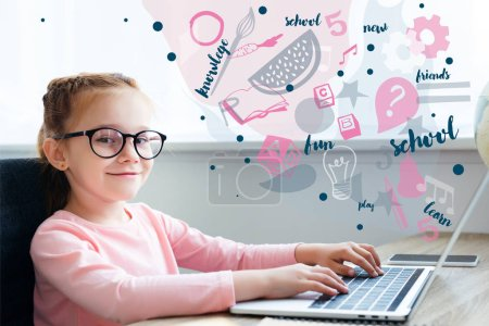 Beautiful kid in eyeglasses using laptop with educational icons