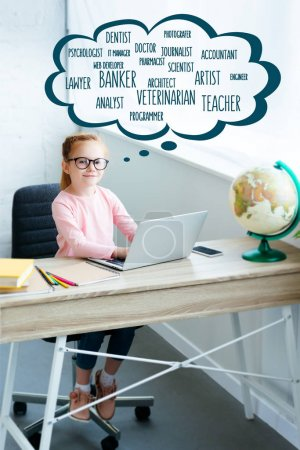 High angle view of child in eyeglasses smiling at camera while using laptop and studying at home with words of different professions in speech bubble