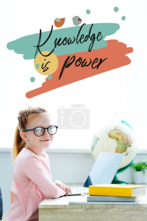 """Photo for Beautiful red haired schoolgirl in eyeglasses smiling at camera while studying with books and laptop, with """"knowledge is power"""" lettering - Royalty Free Image"""
