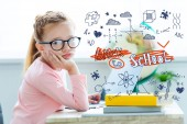 """Bored child in eyeglasses looking at camera while studying with laptop and books with """"back to school"""" lettering and icons"""