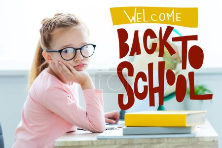 """Bored child in eyeglasses looking at camera while studying with laptop and books, with """"welcome back to school"""" lettering"""