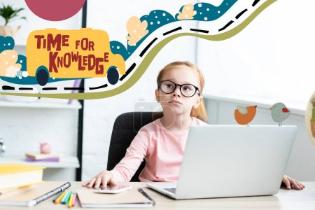 """Photo for Thoughtful little schoolchild in eyeglasses looking up while sitting at desk and using laptop with """"time for knowledge"""" lettering - Royalty Free Image"""