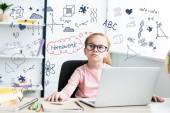 Réfléchie petit écolier à lunettes en levant tandis qu'assis au bureau et à l'aide de portable avec icônes d'apprentissage