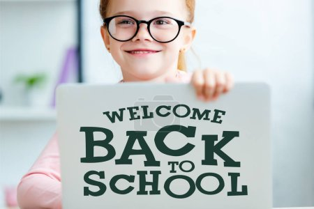 "Adorable red haired schoolgirl in eyeglasses using laptop with ""welcome back to school"" lettering"