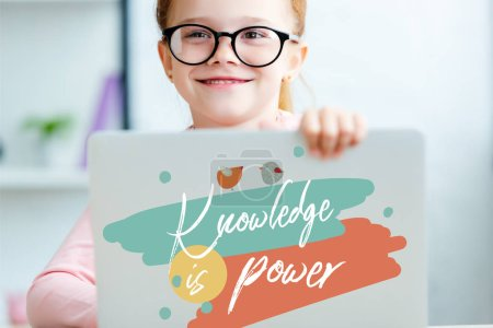 "red haired schoolgirl in eyeglasses using laptop with ""knowledge is power"" lettering"