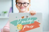 """red haired schoolgirl in eyeglasses using laptop with """"knowledge is power"""" lettering"""