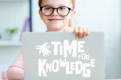 """Adorable red haired schoolgirl in eyeglasses using laptop with """"time for knowledge"""" lettering"""