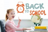 """Cheerful redhead child pointing up with finger and smiling at camera while studying with books and laptop at home with """"back to school"""" lettering with alarm clock"""