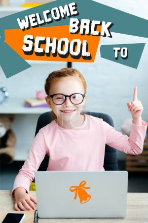 """Adorable red haired schoolgirl in eyeglasses pointing up with finger and smiling at camera while using laptop at home with """"welcome back to school"""" lettering"""