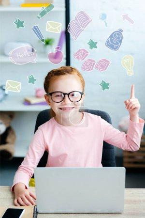 Photo pour Adorable écolière aux cheveux rouge en lunettes de vue vers le haut avec le doigt et souriant à la caméra tout en utilisant le portable à la maison avec icônes éducatifs - image libre de droit