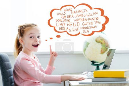 redhead schoolchild studying with books and laptop and pointing up on words on different languages in speech bubble