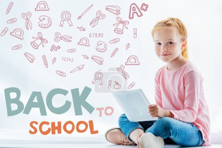 beautiful redhead child using digital tablet, with icons and back to school concept
