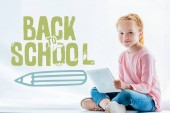 beautiful redhead child using digital tablet and smiling at camera while sitting on windowsill, back to school concept