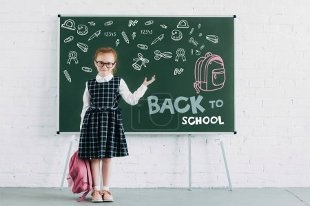 adorable little schoolgirl with backpack showing blackboard with icons and back to school lettering