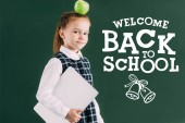 beautiful little schoolgirl with apple on head holding laptop and standing near chalkboard with welcome back to school lettering